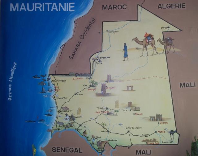 """Mapa de Mauritania en el hotel Atlantique. Nos recordaba M.A. Blasco, de la embajada española, una hermosa cita del aviador y escritor francés Saint-Exupéry, enamorado del desierto y del país: """"Él habrá creído no haber vivido aquí más que una aventura, y reencontrar allí lo esencial, pero descubrirá con disgusto que las únicas riquezas verdaderas las ha poseído aquí, en el desierto: este prestigio de la arena, la noche, este silencio, esta patria del viento y las estrellas"""" (Antoine de Saint-Exupéry, Terre des hommes)"""
